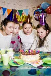 girls blowing candles